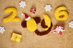 New Year 2016. Christmas.Funny monkey with banana. New Year 2016. Christmas.Funny monkey in Santa hat with banana,presents. Happy vivid festive still life.Yellow stock images