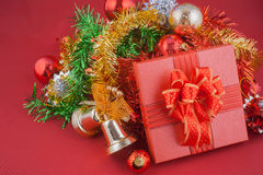 New year and Christmas gift box with decorations on red background Stock Photography