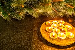 New year and Christmas, green artificial pine on a black background in the light of wax candles. Yellow warm homely touches, the i. Llumination on a circular stock photo