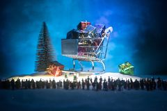 New year or Christmas holiday shopping concept. Store promotions. Silhouette of a large crowd of people watching at a big shopping. Trolley with gifts. People stock photos