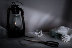 New Year, Christmas. kerosene lamp with fir branches and cones on a table in the twilight Royalty Free Stock Images