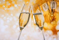 New Year or Christmas at midnight with champagne flutes make cheers, golden bokeh and clock. On golden background Royalty Free Stock Image