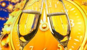New Year or Christmas at midnight with champagne flutes make cheers on golden clock background Royalty Free Stock Image