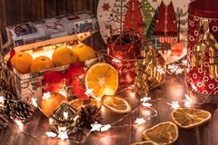 New Year and Christmas mood, New Year`s table decoration, garlands, stars, cones, tangerines royalty free stock photography