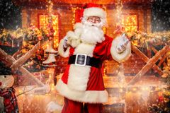 New year and christmas. Portrait of surprised Santa Claus in the courtyard of his house decorated with Christmas lights. Christmas and New Year concept royalty free stock photography