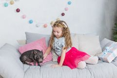 New Year and Christmas story about a little girl in festive clothing and mini pig. Little Pig symbol of 2019. Black royalty free stock photo