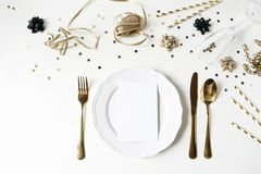New Year, Christmas styled black and gold table setting with plate, cutlery, confetti stars and champagne wine glass royalty free stock images