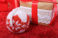 New Year and Christmas theme. Knitted Christmas ball on a Christmas tree. Christmas  ball with white red ornament. Christmas gift tied with red ribbon and a Stock Photography