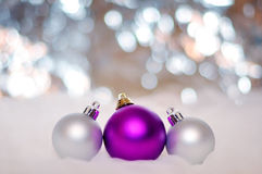 NEW YEAR, CHRISTMAS: Three Purple and Silver Balls. Merry Christmas Balls with Bokeh Background Stock Photo