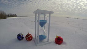 New Year and Christmas time concept. Beautiful hourglass sandglass and Christmas baubles on field, time la stock footage