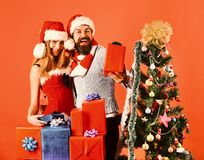 New Year and Christmas time concept. Santa and girl. With xmas gift boxes. Couple in love with red and blue presents near fir tree. Man with beard and women stock images