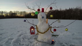 New Year Christmas time snowman on field with candles and evening clouds, time lapse 4K stock video footage