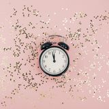 New Year Christmas Top view flat lay black alarm clock twelve covered golden stars confetti copy space millennial pink color paper. Background minimal style stock photo