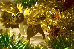 New Year and Christmas toy deer in celebratory tinsel royalty free stock photography