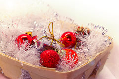 New year Christmas . Toys in a basket, red spheres, pine cones, sweet candies of a toy. Stock Image