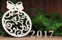 New year 2017,Christmas-tree decoration with a branch of a fir-tree and wooden figures of the coming year, Royalty Free Stock Photography