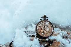 New year clock before midnight. Antique pocket watch in the snow.  royalty free stock photos