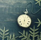 New year clock. Old pocket watch on a wooden background. New Year`s background with hours over time 23:55 Royalty Free Stock Image
