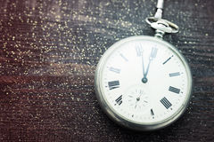 New year clock. Old pocket watch on a wooden background. Royalty Free Stock Image