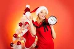 New year clock - time christmas. Happy girl preparing to celebrate new year and merry christmas. Isolated, red. Background stock photo