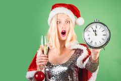 New year clock - time christmas. Surprised woman celebrate new year and merry christmas. Celebration champagne. Isolated. Green background royalty free stock image