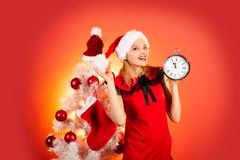 New year clock - time christmas. Woman celebration Christmas on red background. New year party. Christmas clock concept. New year clock - time christmas. Woman stock photo
