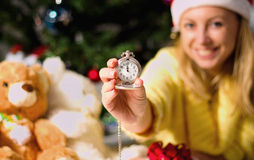New Year clock in woman hands. On christmas tree background Royalty Free Stock Photography