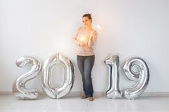 New 2019 Year is coming. Cheerful young woman standing near silver colored numbers and sparklers in white room stock images