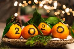 New Year 2020 is Coming Concep. T. Numbers written in Black Ink on the Oranges that are laying in the Basket with Pine Sticks and Xmas Lights on the Background royalty free stock photography
