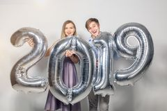 New 2019 Year is coming concept - Cheerful young man and woman are holding silver colored numbers stock photography