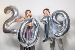 New 2019 Year is coming concept - Cheerful young man and woman are holding silver colored numbers stock photos