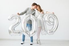 New 2019 Year is coming concept - Cheerful young man and woman are holding silver colored numbers royalty free stock photo