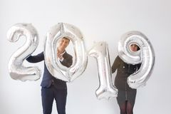 New 2019 Year is coming concept - Cheerful young man and woman are holding silver colored numbers royalty free stock photos