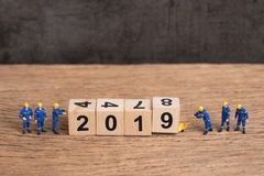 New year 2019 is coming concept, cute miniature people uniform worker staffs finish building cube wooden block as year number 2019 royalty free stock photos