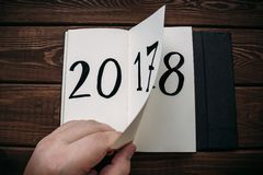 New Year 2018 is coming concept. Hand flips notepad sheet on wooden table. 2017 is turning, 2018 is opening Royalty Free Stock Images