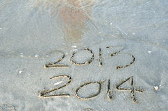 New Year 2014 is coming concept. Inscription 2013 and 2014 on a beach sand Royalty Free Stock Photo