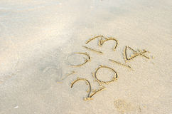 New Year 2014 is coming concept. Inscription 2013 and 2014 on a beach sand Stock Photos
