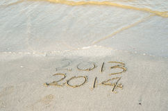 New Year 2014 is coming concept. Inscription 2013 and 2014 on a beach sand Royalty Free Stock Images