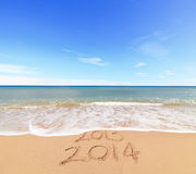 New Year 2014 is coming. Concept - inscription 203 and 2014 on a beach sand, the wave is covering digits 2013 Royalty Free Stock Image