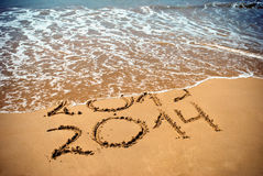 New Year 2014 is coming concept. Inscription 2013 and 2014 on a beach sand, the wave is covering digits 2013 Royalty Free Stock Photography