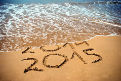 New Year 2015 is coming concept - inscription 2014 and 2015 on a beach sand. The wave is covering digits 2014 Stock Photos