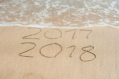 New Year 2018 is coming concept - inscription 2017 and 2018 on a beach sand, the wave is almost covering the digits 2017 stock photography