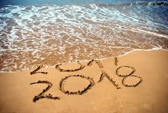 New Year 2018 is coming concept - inscription 2017 and 2018 on a beach sand, the wave is covering digits 2017. New Year 2018 celeb. Ration on New Year`s Eve Royalty Free Stock Images