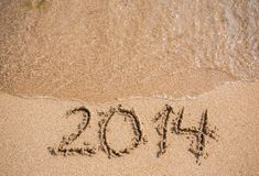 New Year 2014 is coming concept. Inscription 2013 and 2014 on a beach sand, the wave is starting to cover the digits 2013 Stock Photos
