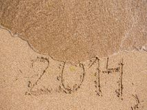 New Year 2014 is coming concept. Inscription 2013 and 2014 on a beach sand, the wave is starting to cover the digits 2013 Royalty Free Stock Photos