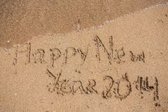 New Year 2014 is coming concept. Inscription 2013 and 2014 on a beach sand, the wave is starting to cover the digits 2013 Stock Photography