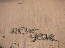 New Year 2014 is coming concept. Inscription 2013 and 2014 on a beach sand, the wave is starting to cover the digits 2013 Stock Photo