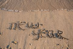 New Year 2014 is coming concept. Inscription 2013 and 2014 on a beach sand, the wave is starting to cover the digits 2013 Royalty Free Stock Photography