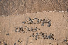 New Year 2014 is coming concept. Inscription 2013 and 2014 on a beach sand, the wave is starting to cover the digits 2013 Royalty Free Stock Image