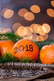 New Year 2018 is Coming Concept. Numbers written in Black Ink on the Oranges that are laying in the Basket with Pine Sticks and Xmas Lights on the Background stock images